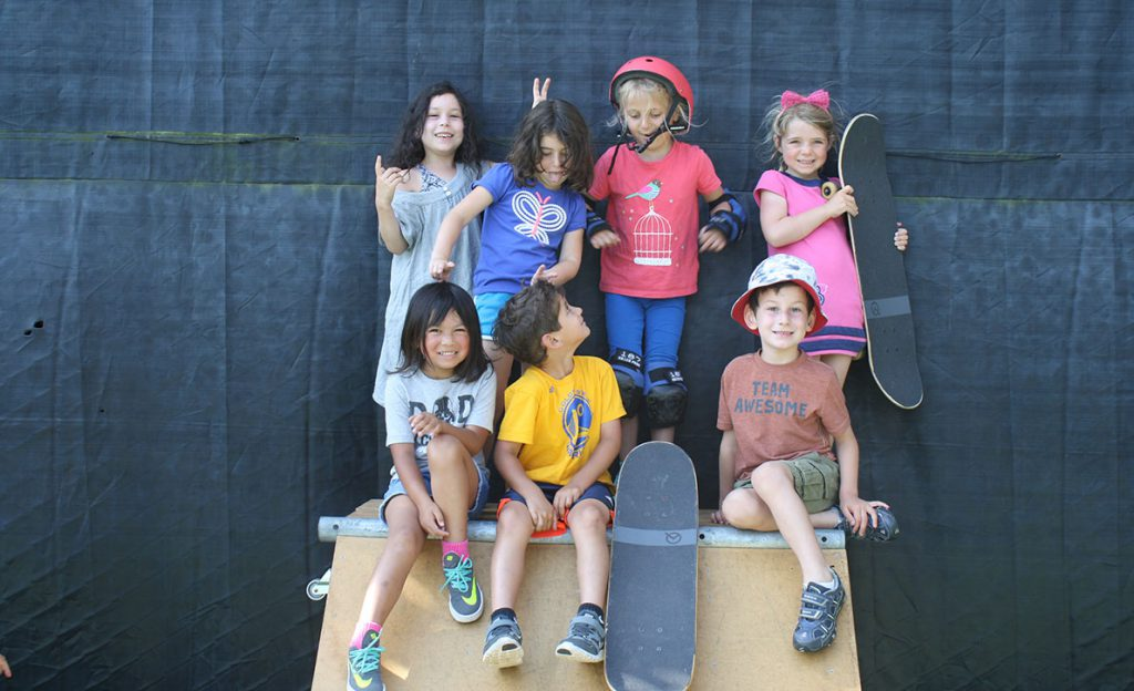 Kids posing with a skateboard