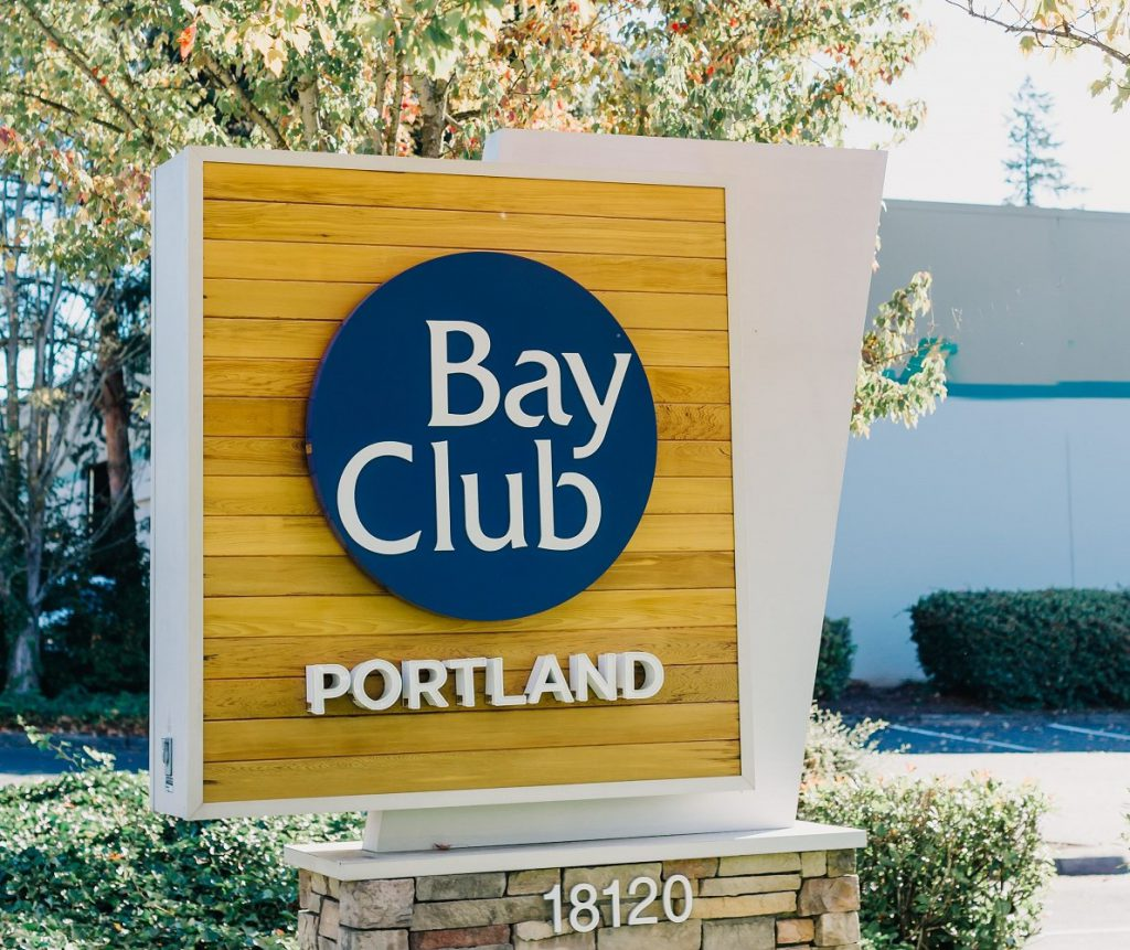 Welcome! We hope you enjoy your visit. Wooden corner sign with Bay Club Portland logo.